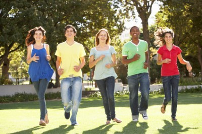 Group Of Teenagers Running Through Park